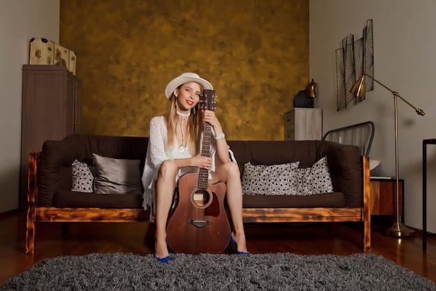 Piękna młoda kobieta z gitarą we wnętrzu pokoju. śliczna kobieta na kanapie z gitarą w jej rękach. koncepcja nauki w domu lub gry na gitarze w domu. miejsce objęte prawami autorskimi dla witryny, banera lub logo