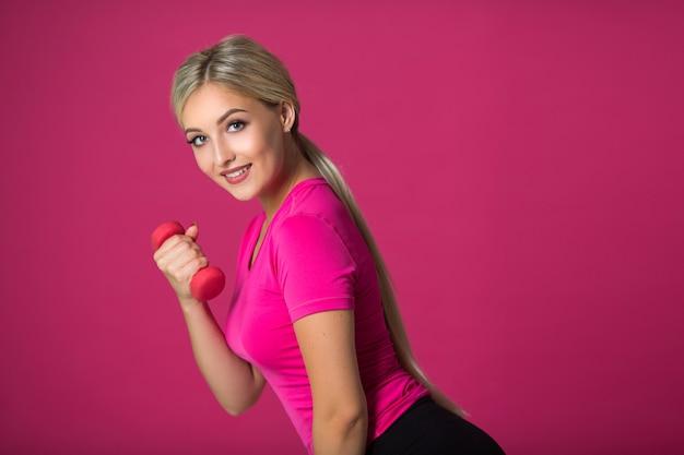 Piękna młoda kobieta z hantlami w rękach na różowo
