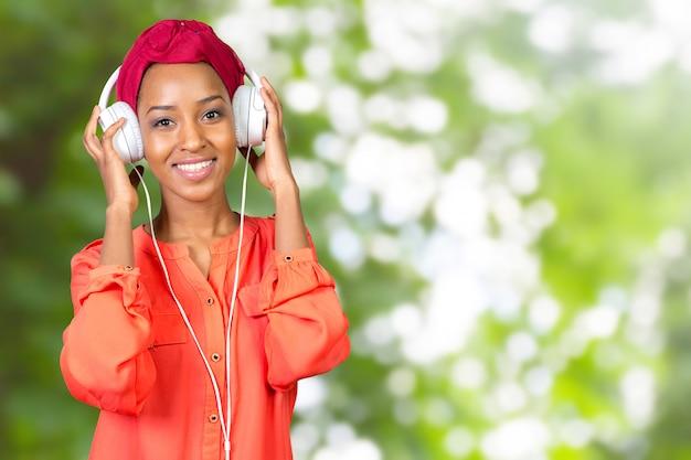 Piękna młoda kobieta z hełmofonami i urządzeniem mobilnym