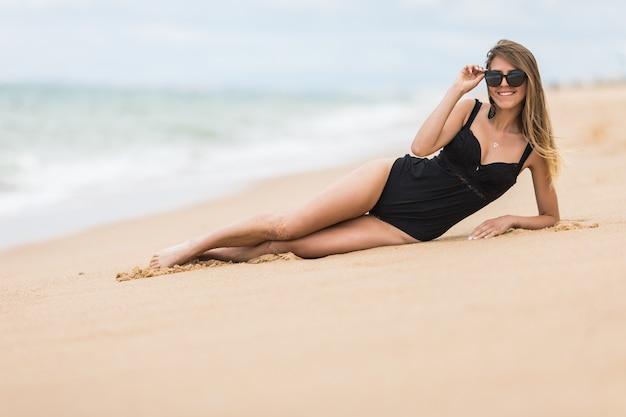 Piękna młoda kobieta z idealnym ciałem, leżąc na plaży