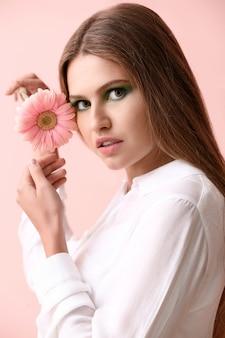 Piękna młoda kobieta z jasnym makijażem i kwiatem
