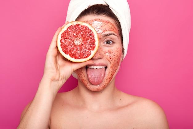 Piękna młoda kobieta z jasnym peelingiem na twarzy trzyma w jednej ręce połowę grejpfruta rzepaku, wystaje jej język, mając biały ręcznik na głowie, wygląda świeżo i zachwycona. koncepcja pielęgnacji skóry.
