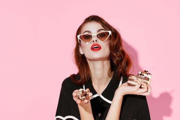 Piękna młoda kobieta z jedzeniem w jej rękach, kobieta je w studiu, koloru tło, bez diet