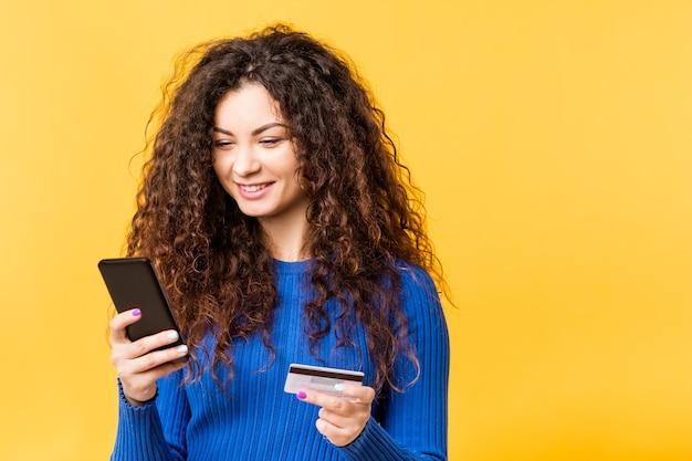 Piękna młoda kobieta z karty kredytowej smartphone. transakcja zakupów online. miejska bezgotówkowa metoda bankowości mobilnej