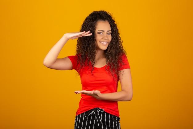 Piękna młoda kobieta z kędzierzawym włosy mieniem coś w rękach