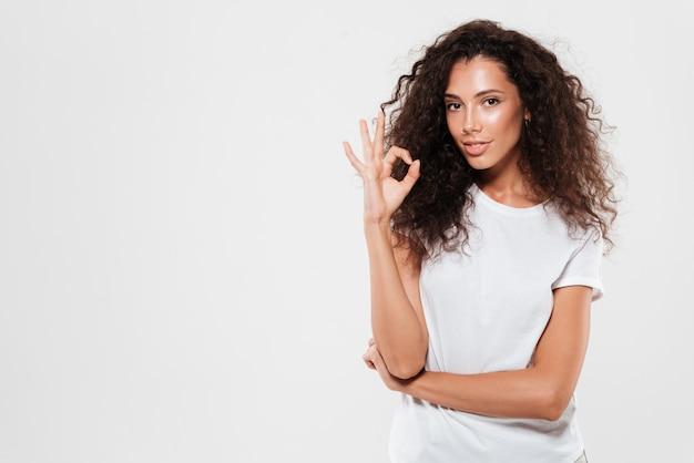 Piękna młoda kobieta z kędzierzawym włosy pokazuje ok