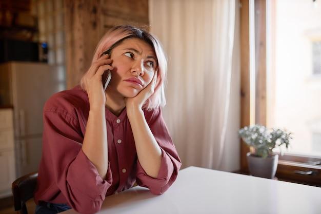 Piękna młoda kobieta z kolczykiem w nosie i różowymi włosami siedzi przy stole, rozmawia przez telefon