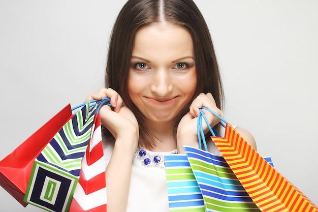 Piękna młoda kobieta z kolorowymi torbami na zakupy na szarym tle