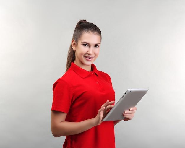 Piękna młoda kobieta z komputera typu tablet na jasnej powierzchni
