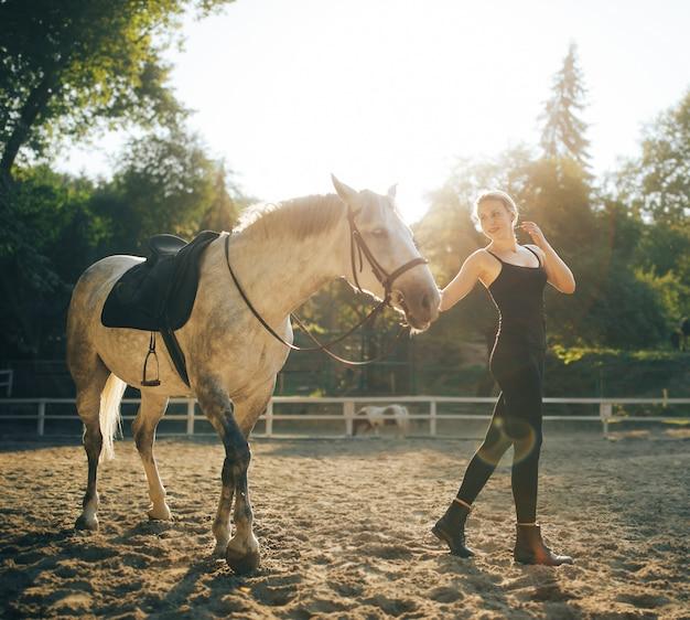 Piękna młoda kobieta z koniem plenerowym