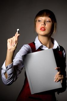 Piękna młoda kobieta z kopertą na papiery pisze kredą na niewidzialnej tablicy kredowej