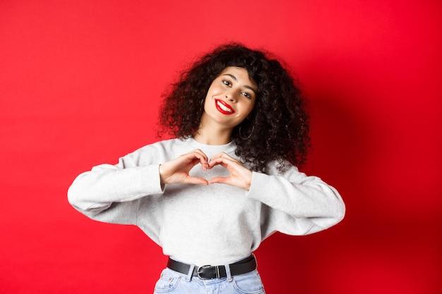 Piękna młoda kobieta z kręconymi włosami, pokazując gest serca, powiedzieć, że kocham cię i uśmiechać się romantycznie do kamery, stojąc na czerwonym tle.