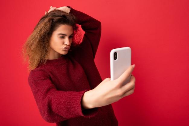 Piękna młoda kobieta z kręconymi włosami ubrana w ciemnoczerwony sweter na tle ściany na czerwonym tle