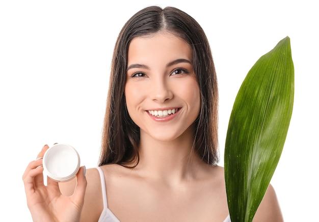 Piękna młoda kobieta z kremem do twarzy i tropikalnym liściem na białym tle
