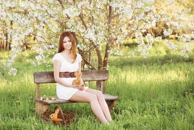 Piękna młoda kobieta z królikami w ogródzie