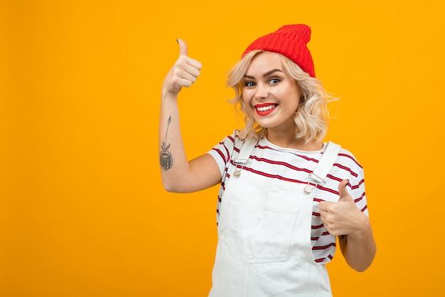 Piękna młoda kobieta z krótkimi blond kręconymi włosami i jasnym makijażem w białych kombinezonach i czerwonym kapeluszu lubi coś i uśmiecha się, portret na pomarańczowo