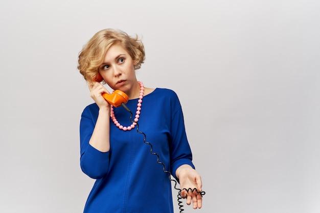 Piękna młoda kobieta z krótkimi falującymi blond włosami w klasycznej niebieskiej sukience trzyma z telefonu słuchawkę retro i rozmawia z zaskoczonym wyrazem twarzy klientów