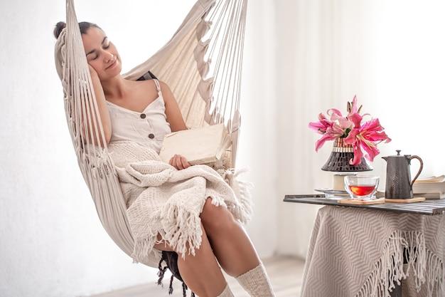 Piękna młoda kobieta z książką w fotelu hamakowym. koncepcja wypoczynku i domowego komfortu.