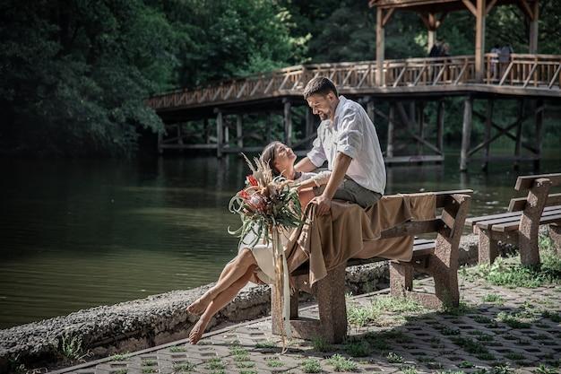 Piękna młoda kobieta z kwiatami i jej mężem siedzą na ławce i cieszą się komunikacją, randką na łonie natury, romansem w małżeństwie.