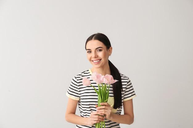 Piękna młoda kobieta z kwiatami na szarej powierzchni