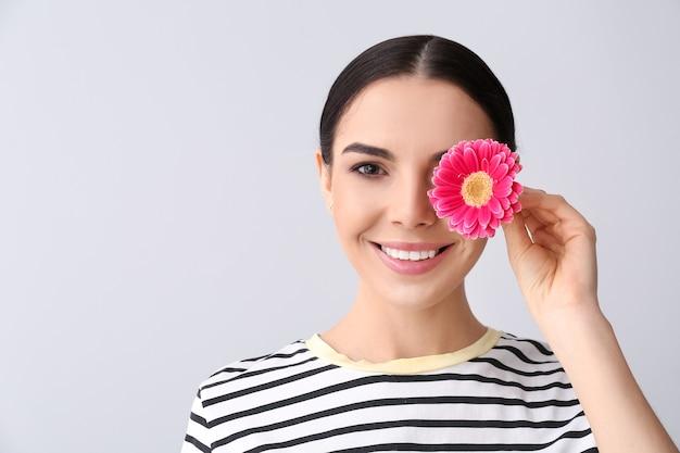 Piękna młoda kobieta z kwiatem na szarej powierzchni