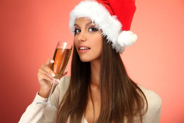 Piękna młoda kobieta z lampką szampana, na czerwonym tle