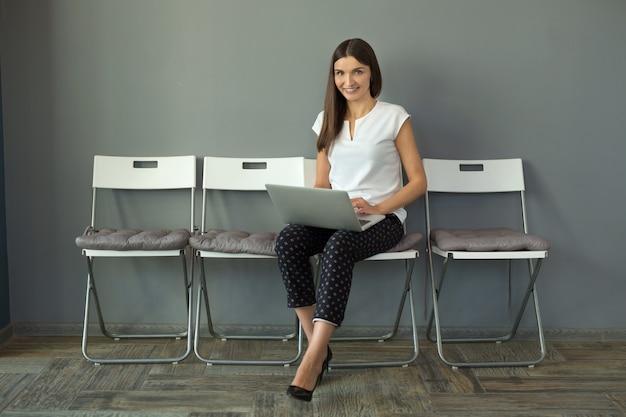Piękna młoda kobieta z laptopem w biurze