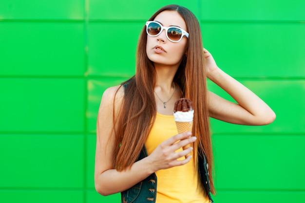 Piękna młoda kobieta z lodami w okularach przeciwsłonecznych stoi w pobliżu zielonej ściany