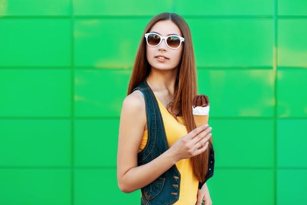 Piękna młoda kobieta z lodami w pobliżu zielonej ściany.
