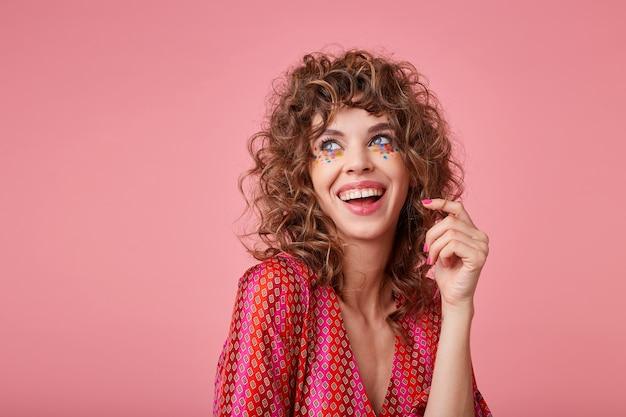 Piękna młoda kobieta z lokami śmiejąca się, będąca w dobrym nastroju, stojąca, ubrana w paski, skręcająca włosy na palcu, odwracająca wzrok