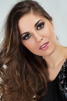 Piękna młoda kobieta z loki i makijaż