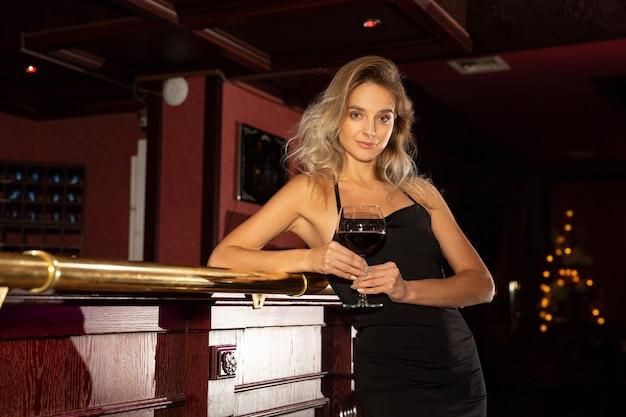 Piękna młoda kobieta z makijażem i fryzurą w czarnej sukience przy lampce wina