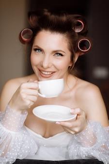 Piękna młoda kobieta z makijażem, lokówki ubrana w białą sukienkę i relaks w domu, trzymając filiżankę kawy lub herbaty