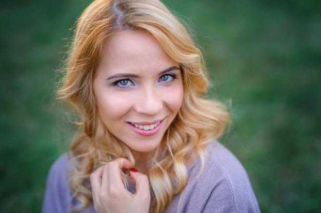 Piękna młoda kobieta z makijażem pozuje w lato parku