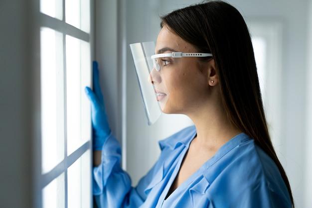 Piękna młoda kobieta z maską wewnątrz szpitala