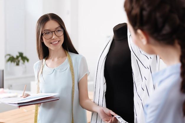 Piękna młoda kobieta z miarką na szyi, stojąca w pobliżu manekina i trzymająca wiszący na nim sweter, patrząc na koleżankę z uśmiechem