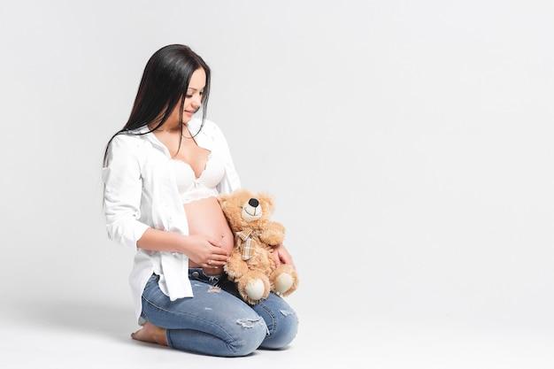 Piękna młoda kobieta z misiem siedzącym na podłodze na białej ścianie