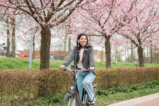 Piękna młoda kobieta z mniejszości ras mieszanych, jazda na rowerze w rozkwicie wiosną w ubranie z atrakcyjnym uśmiechem. portret rekreacyjny styl życia.