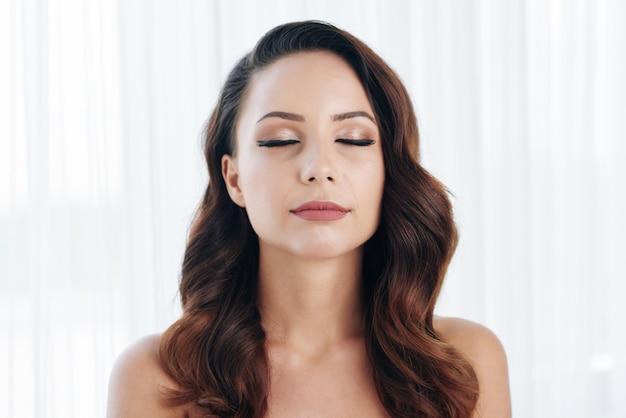 Piękna młoda kobieta z nagimi ramionami pozuje z zamkniętymi oczami