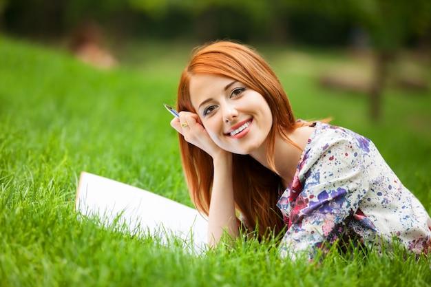 Piękna młoda kobieta z notatką przy plenerowym