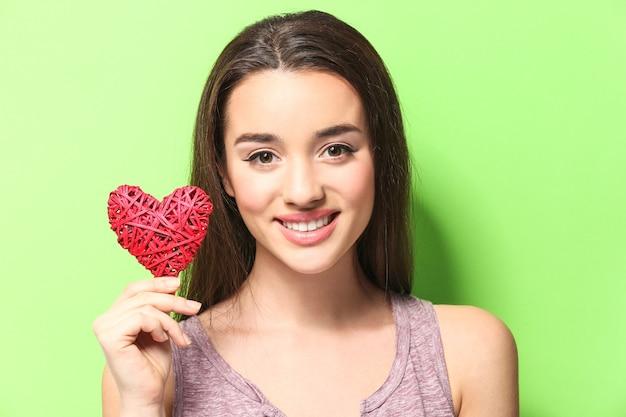 Piękna młoda kobieta z ozdobnym wiklinowym sercem na kolorowym tle
