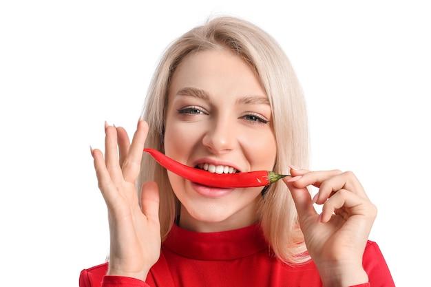 Piękna młoda kobieta z papryczką chili na białej powierzchni