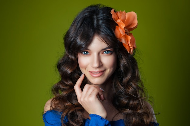 Piękna młoda kobieta z pięknymi falowanymi włosami z dużym kwiatem we włosach na zielonym tle