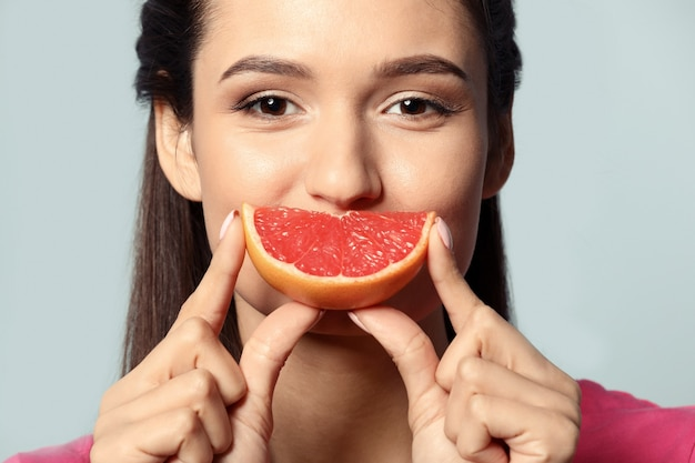 Piękna młoda kobieta z plasterkiem owoców cytrusowych na kolorowym tle, zbliżenie