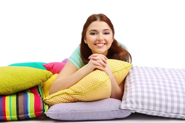 Piękna młoda kobieta z poduszkami na białym tle