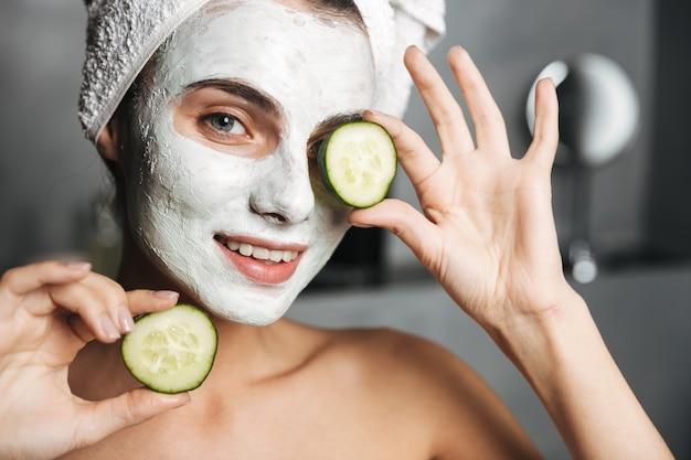 Piękna młoda kobieta z ręcznikiem owiniętym wokół głowy na sobie maskę