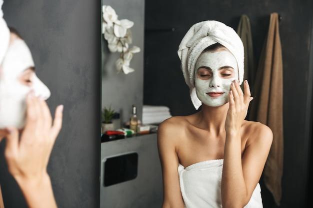 Piękna młoda kobieta z ręcznikiem owiniętym wokół głowy, stosując maskę w łazience