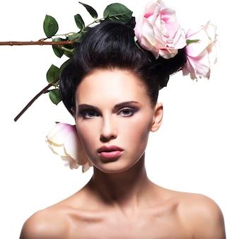 Piękna młoda kobieta z różowe kwiaty we włosach - na białym tle