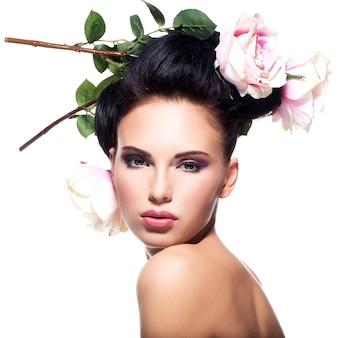 Piękna młoda kobieta z różowe kwiaty we włosach - na białym tle.
