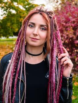 Piękna młoda kobieta z różowymi dredami kanekalon patrząc na kamery i uśmiechnięty
